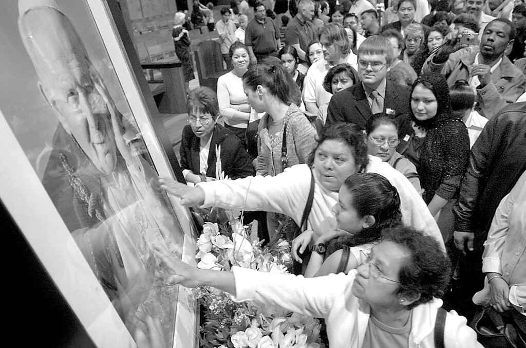 . 4/2/05--LOS ANGELES-- Parishioners crush together to touch a portrait of the deceased Pope John Paul II following Saturday\'s mass at Cathedral of Our lady of the Angels in downtown Los Angeles.   (Michael Owen Baker/Los Angeles Daily News)