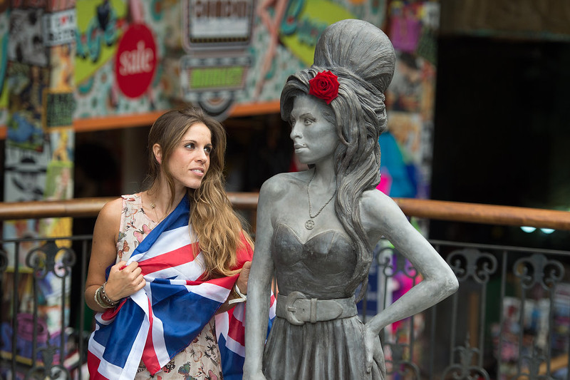 . A fan poses for a picture with a new statue of the late singer Amy Winehouse after it was unveiled in Camden\'s Stables Market, in London, England, Sunday, Sept. 14, 2014. Three years after her death the unveiling coincides with what would have been her 31st birthday. (AP Photo/Tim Ireland)