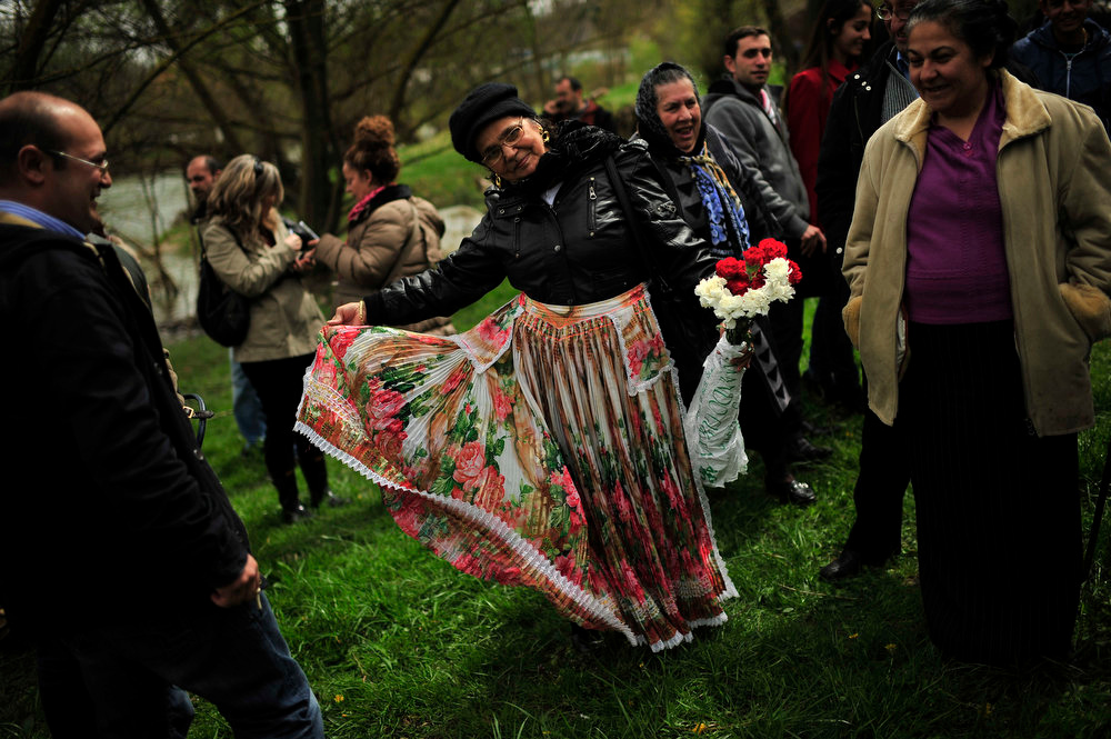 . A gypsy woman dances with her flowers during a ceremony beside the Arga River in honor of their ancestors on the Day of the Gypsy, in Pamplona northern Spain on Monday, April 8, 2013. (AP Photo/Alvaro Barrientos)