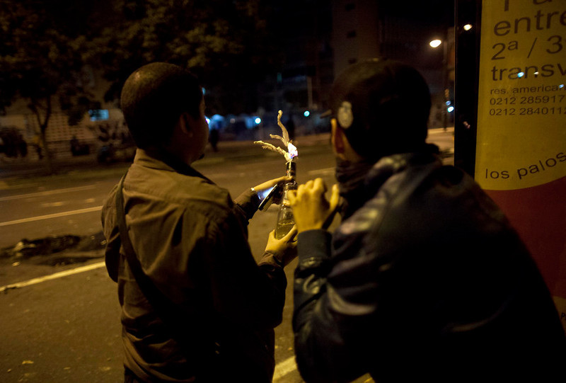 . Demonstrators prepare a fire bomb during clashes with National Guard as they protest against the official results of last Sunday\'s presidential elections in downtown Caracas, Venezuela, Monday, April 15, 2013. National Guard troops fired tear gas and plastic bullets to disperse demonstrators protesting the official results in Venezuela\'s disputed presidential election.   (AP Photo/Ramon Espinosa)