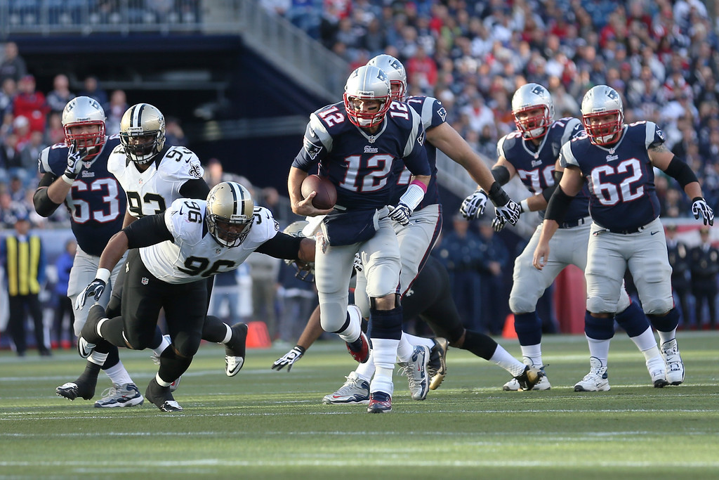 . Quarterback Tom Brady #12 of the New England Patriots rushes the ball while being chased by defensive tackle Tom Johnson #96 of the New Orleans Saints during the first half at Gillette Stadium on October 13, 2013 in Foxboro, Massachusetts.  (Photo by Rob Carr/Getty Images)