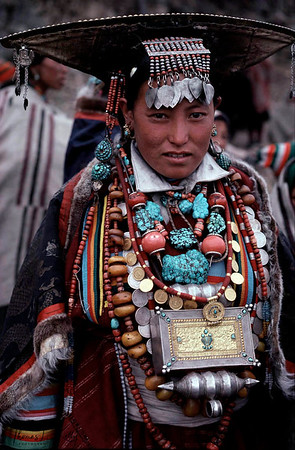 Displaying family wealth with necklaces of amber, coral, conch, and turquoise, the women wear in herited gaus, portable alters, around their necks, and headdresses showing the influence of such western Himalayan Kingdom as Ladakh. Their rainbow trimmed robes, unique to the region.  