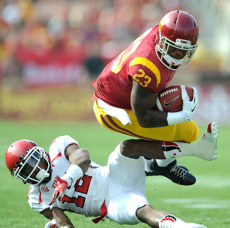 . Southern California running back Tre Madden (23) leaps over Utah defensive back Justin Thomas (12) fir a first down during the first half of an NCAA college football game in the Los Angeles Memorial Coliseum in Los Angeles, on Saturday, Oct. 26, 2013.  (Photo by Keith Birmingham/Pasadena Star-News)
