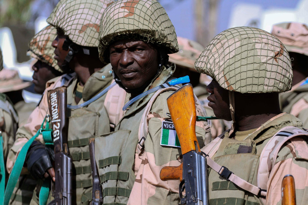 Description of . Nigerian Army soldiers stand as part of preparations for deployment to Mali, at the Nigerian Army peacekeeping centre in Jaji, near Kaduna January 17, 2013. French troops launched their first ground assault against Islamist rebels in Mali on Wednesday in a broadening of their operation against battle-hardened al Qaeda-linked fighters who have resisted six days of air strikes. West African military chiefs said the French would soon be supported by around 2,000 troops from Nigeria, Chad, Niger and other regional powers - part a U.N.-mandated deployment which had been expected to start in September but was kick-started by the French intervention. REUTERS/Afolabi Sotunde