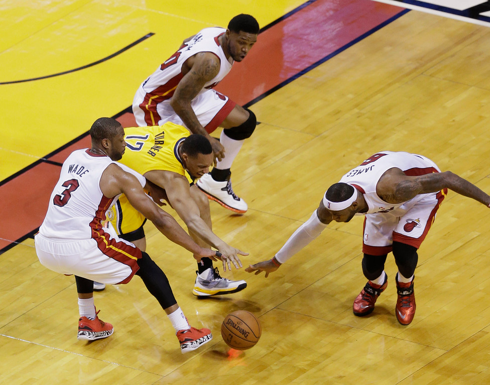 . Indiana Pacers forward Evan Turner (12) loses the ball as Miami Heat guard Dwyane Wade (3) and forward LeBron James (6) attempt to take control during the first half of Game 3 in the NBA basketball Eastern Conference playoff series, Saturday, May 24, 2014 in Miami. At top is Heat forward Udonis Haslem. (AP Photo/Wilfredo Lee)