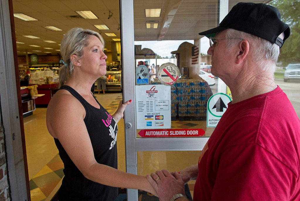 . Noel Michael, left, is comforted by neighbor Ruffin Griffin as she talked about her flooded home at the Carter\'s Supermarket in Livingston, La., Monday, Aug. 15, 2016. Micheal and her husband and son were volunteering at the supermarket to keep their mind off of their flood damaged home. (AP Photo/Max Becherer)