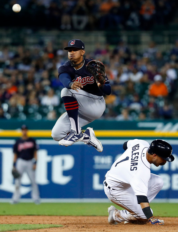 . Cleveland Indians shortstop Francisco Lindor, top, throws to first base after completing the force on Detroit Tigers\' Jose Iglesias (1) at second base in the ninth inning of a baseball game in Detroit, Friday, July 27, 2018. Cleveland won 8-3. (AP Photo/Paul Sancya)