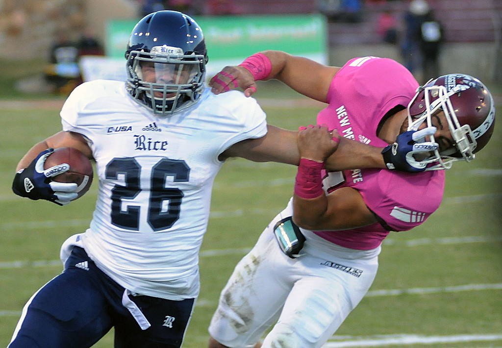 . Rice running back Turner Petersen stiffs arms New Mexico State University\'s  Davis Cazares during an NCAA college football game Saturday, Oct. 19, 2013 at Aggie Memorial Stadium in Las Cruces, N.M. (AP Photo/The Las Cruces Sun-News, Robin Zielinski)
