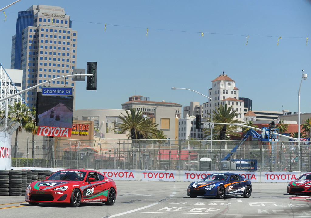 . 04-19-2013-(LANG Staff Photo by Sean Hiller)- Adam Corolla, in the red car, rounds turn 1 during practice for the Toyota Pro/Celebrity Race at the Toyota Grand Prix Friday in Long Beach.