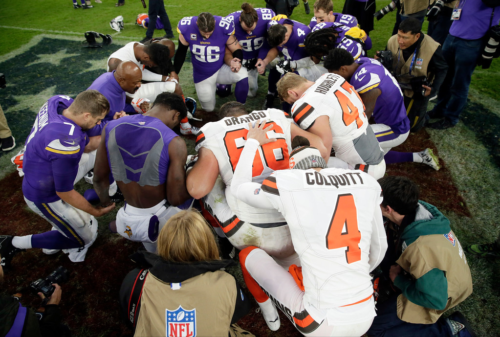 . Cleveland Browns and Minnesota Vikings players pray on the field after an NFL football game at Twickenham Stadium in London, Sunday Oct. 29, 2017. The Vikings won 33-16. (AP Photo/Tim Ireland)