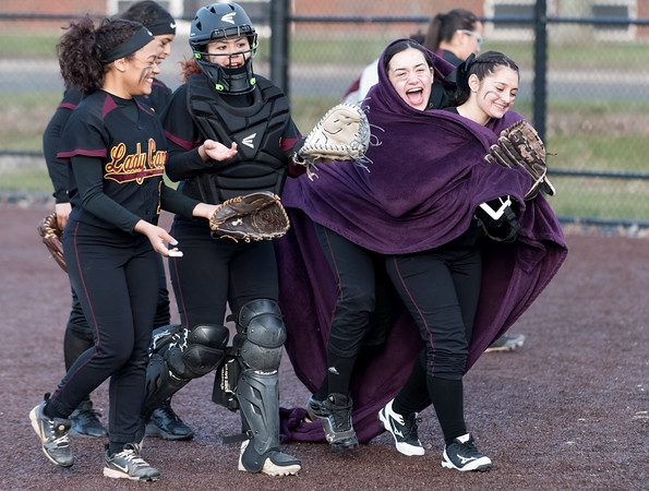 04/05/18 Wesley Bunnell   Staff New Britain softball defeated Newington on Thursday afternoon at Chesley Park for the schools first win over Newington in 11 games. Wearing a blanket on the field between innings Amanda Jacobs (5) celebrates with teammates.