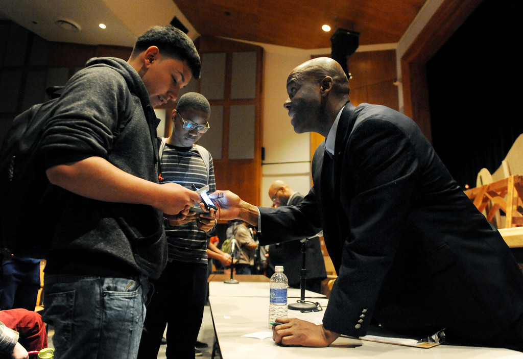 . Jeff Fard, right, exchanges information with students at George Washington High School on March 26 after a panel of Black Men in Support of Education, a group of successful black men who mentor kids, spoke to students about life and the journey to success. Denver, Colo. Photo by Jamie Cotten, Special to The Denver Post