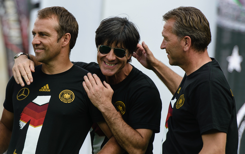 . (R-L) Germany\'s goalkeepers\' coach Andreas Koepke, Germany\'s coach Joachim Loew and Germany\'s assistant coach Hans-Dieter Flick celebrate during a victory parade of Germany\'s football national team on July 15, 2014 at Berlin\'s landmark Brandenburg Gate to celebrate their FIFA World Cup title. Germany won their fourth World Cup title, after their 1-0 win over Argentina on July 13, 2014 in Rio de Janeiro in the FIFA World Cup Brazil final game. (CLEMENS BILAN/AFP/Getty Images)