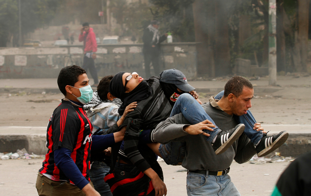 Description of . TOPSHOTS Egyptians protesters carrying a wounded youth during clashes near Cairo's Tahrir Square on January 28, 2013. Egypt's cabinet approved a draft law that would allow President Mohamed Morsi to deploy the armed forces on the streets