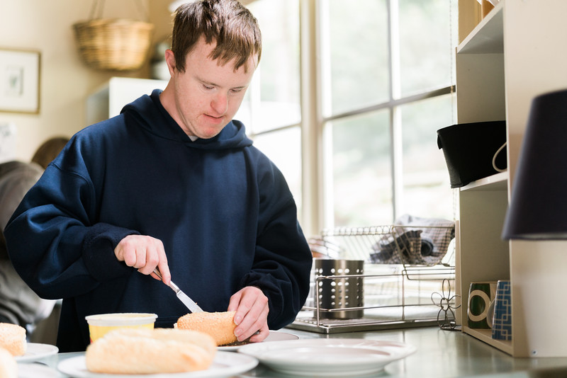 Man cutting a Bread Roll in his Kitchen