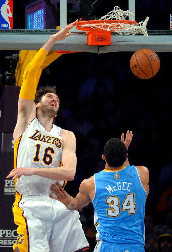 . Los Angeles Lakers forward Pau Gasol, left, of Spain, dunks as Denver Nuggets center JaVale McGee defends dunks during the first half of their NBA basketball game, Sunday, Jan. 6, 2013, in Los Angeles.  (AP Photo/Mark J. Terrill)