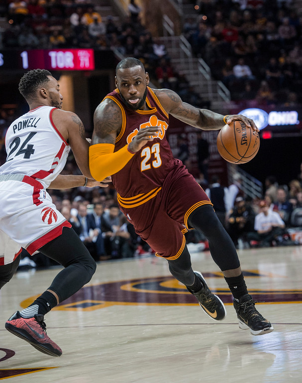 . Cleveland Cavaliers\' LeBron James (23) drives past Toronto Raptors\' Norman Powell (24) during the first half of an NBA basketball game in Cleveland, Tuesday, Nov. 15, 2016. (AP Photo/Phil Long)