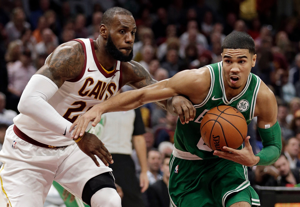 . Boston Celtics\' Jayson Tatum, right, drives past Cleveland Cavaliers\' LeBron James in the first half of an NBA basketball game, Tuesday, Oct. 17, 2017, in Cleveland. (AP Photo/Tony Dejak)