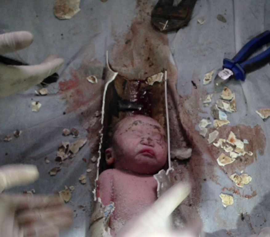 . This frame grab taken from AFPTV footage received on May 28, 2013 shows rescue workers breaking away bits of a pipe to remove a newborn baby boy stuck inside in the city of Jinhua, in the eastern province of Zhejiang.   AFP PHOTO / AFPTVAFPTV/AFP/Getty Images