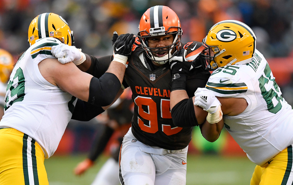 . Cleveland Browns defensive end Myles Garrett, center, squeezes between Green Bay Packers offensive tackle David Bakhtiari, left, and offensive guard Lane Taylor in the second half of an NFL football game, Sunday, Dec. 10, 2017, in Cleveland. The Packers won 27-21 in overtime. (AP Photo/David Richard)