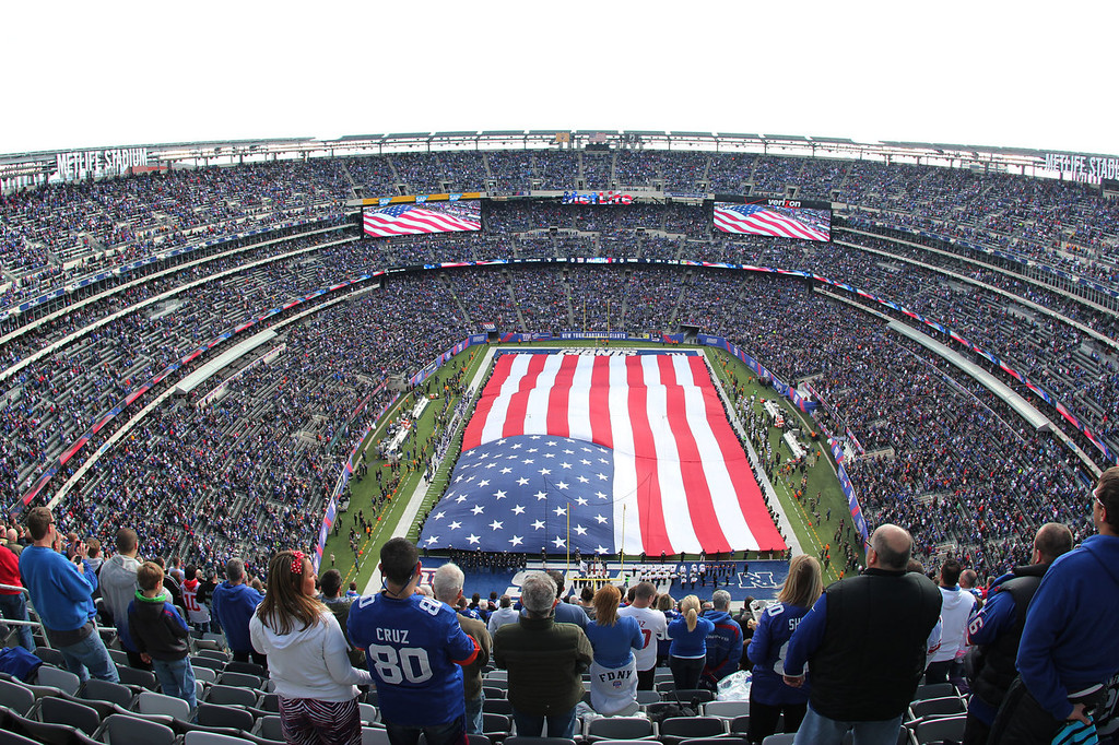 . In this photograph taken with a fisheye lens, a United States flag covers the field at MetLife Stadium as the New York Giants observe the NFL\'s Salute to Service before a football game between the Giants and the Oakland Raiders, Sunday, Nov. 10, 2013, in East Rutherford, N.J. (AP Photo/Paul Kazdan)