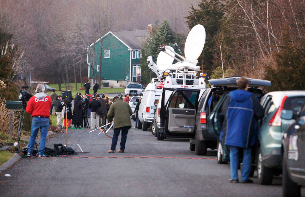 . Members of the media interview neighbours near the secondary crime scene following a shooting at Sandy Hook Elementary School, in Sandy Hook, Connecticut, December 14, 2012. The peace and security of the suburban Connecticut community of Newtown lay shattered on Friday after a gunman attacked a primary school in one of the worst mass shootings in U.S. History. Tearful parents and children gathered around Sandy Hook Elementary School by midday on Friday, surrounded by police vehicles, as young and old alike struggled to make sense of a shooting rampage that killed at least 28 people, including 20 children. REUTERS/Michelle McLoughlin