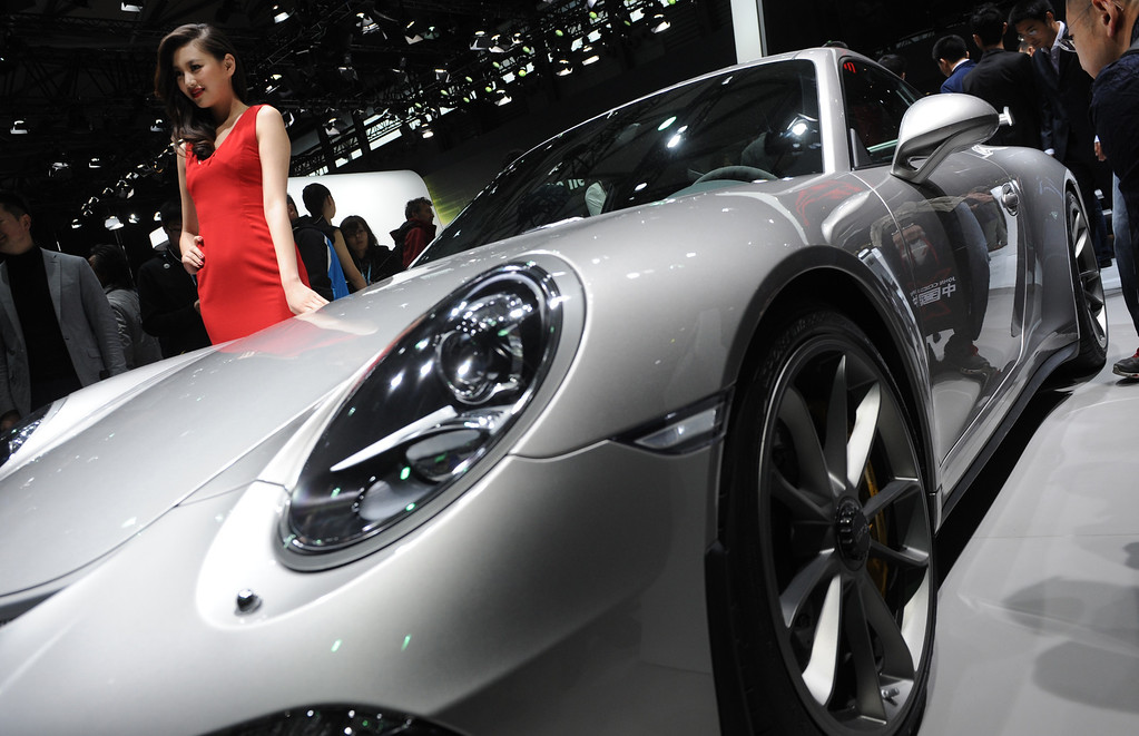. This photo taken on April 20, 2013 shows a model posing next to a Porsche 911 GT3 on media day at the Shanghai auto show. The Shanghai auto show, which opens to the public on April 21, is expected to attract more than 800,000 visitors over the course of nine days.    PETER PARKS/AFP/Getty Images