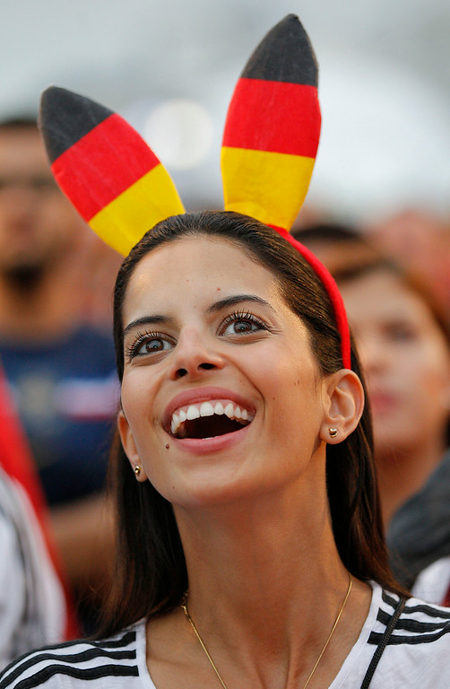 . A Soccer fan, wearing rabbit ears with Germany team\'s colors watches the World Cup round of 16 match of Germany against Algeria on a live telecast inside the FIFA Fan Fest area on Copacabana beach in Rio de Janeiro, Brazil, Monday, June 30, 2014. (AP Photo/Leo Correa)