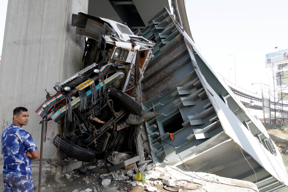 . A policeman stands near a mangled truck at the site where a section of a bridge collapsed early morning in Kolkata, India, Sunday, March 3, 2013. Three persons traveling in the truck that was passing through the bridge were seriously injured in the accident. (AP Photo/Bikas Das)