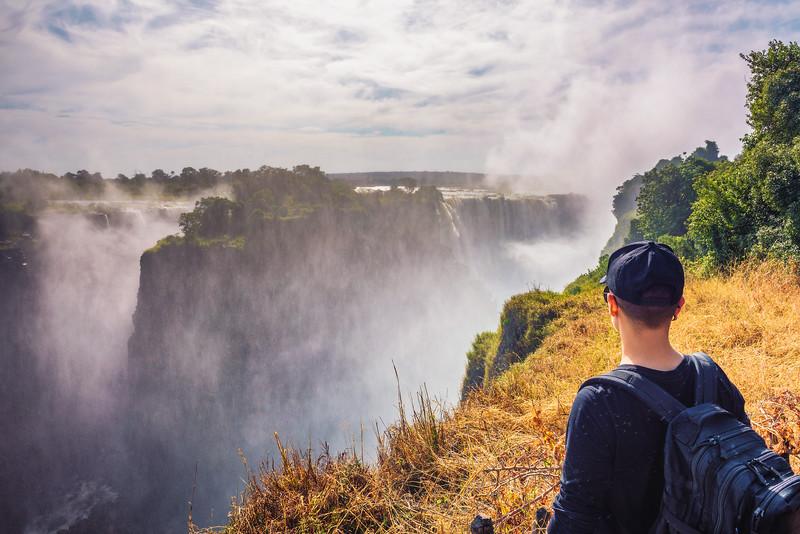 Tourist looks at the Victoria Falls on Zambezi River in Zimbabwe