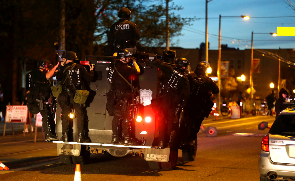 . Seattle Police officers ride on an armored vehicle as they move into position during a May Day march that began as an anti-capitalism protest and turned into demonstrators clashing with police, Wednesday, May 1, 2013, in downtown Seattle. (AP Photo/Ted S. Warren)