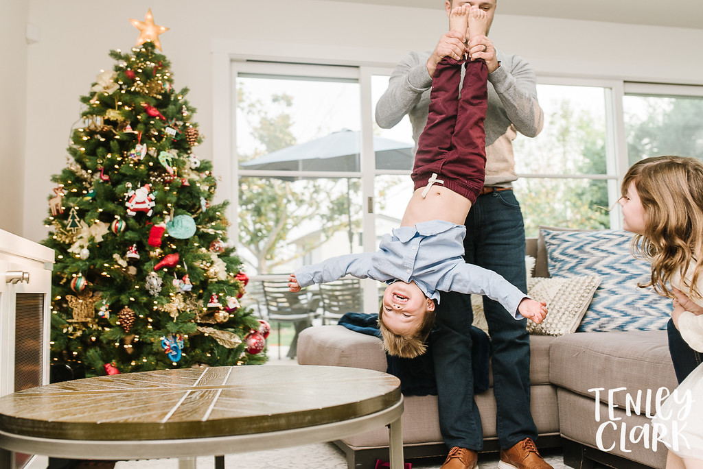 Boy being swung by feet in front of Christmas tree. Lifestyle in-home family photoshoot in Marin, CA by Tenley Clark Photography.