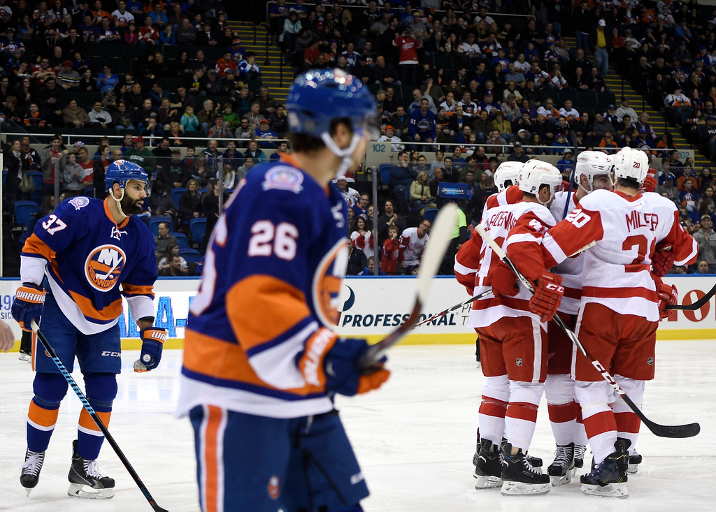 . New York Islanders defenseman Brian Strait (37) and center Tyler Kennedy (26) watch Detroit Red Wings right wing Luke Glendening (41), left wing Drew Miller (20) and others celebrate Miller\'s goal in the first period of an NHL hockey game on Sunday, March 29, 2015, in Uniondale, N.Y. (AP Photo/Kathy Kmonicek)