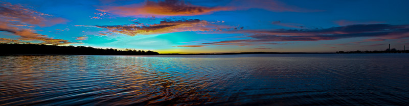 Vivid colored coastal sunrise cloudscape panorama.
