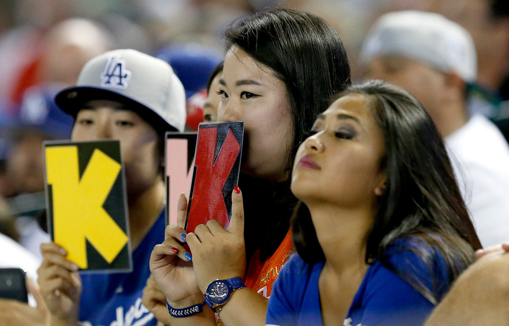 . Los Angeles Dodgers fans record the strikeouts by Hyun-Jin Ryu, of South Korea, against the Arizona Diamondbacks in the third inning of a baseball game on Monday, Sept. 16, 2013, in Phoenix. (AP Photo/Ross D. Franklin)