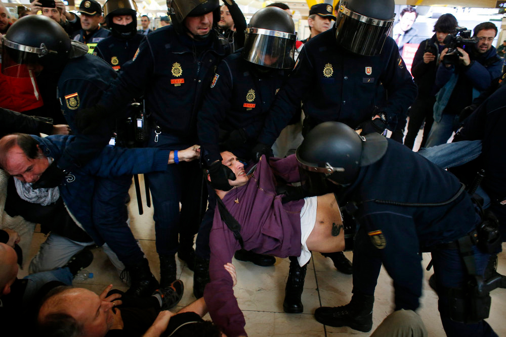 . Spanish riot police officers remove an Iberia airline worker from Terminal 4 at Madrid\'s Barajas airport February 18, 2013. Striking union workers clashed with police at the airport on Monday on the first day of a week-long strike over more than 3,800 pending job cuts at Spain\'s flagship airline Iberia. REUTERS/Susana Vera