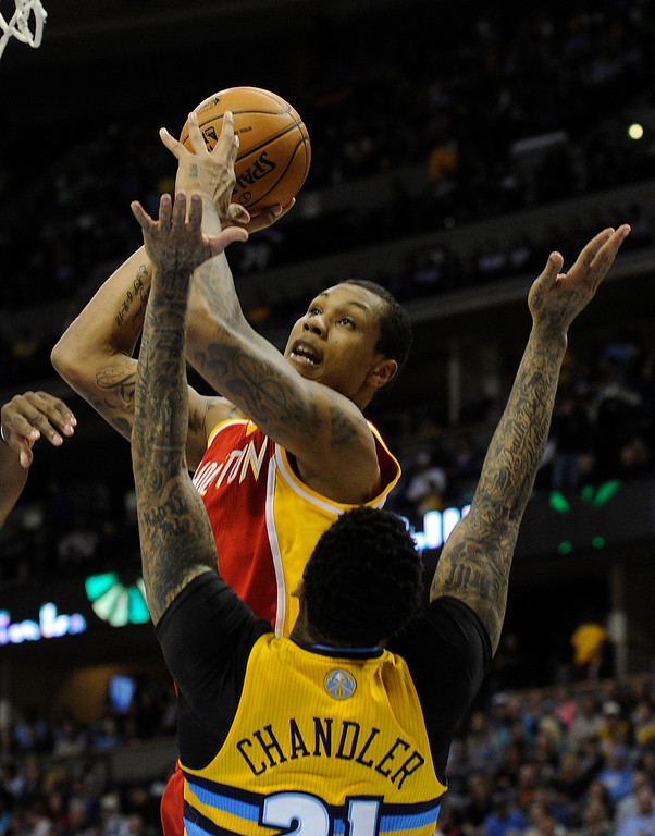 . DENVER, CO. - APRIL 6: Greg Smith (4) of the Houston Rockets drove against Wilson Chandler (21) of the Denver Nuggets in the first half. The Denver Nuggets hosted the Houston Rockets at the Pepsi Center Saturday night, April 6, 2013. Photo By Karl Gehring/The Denver Post)