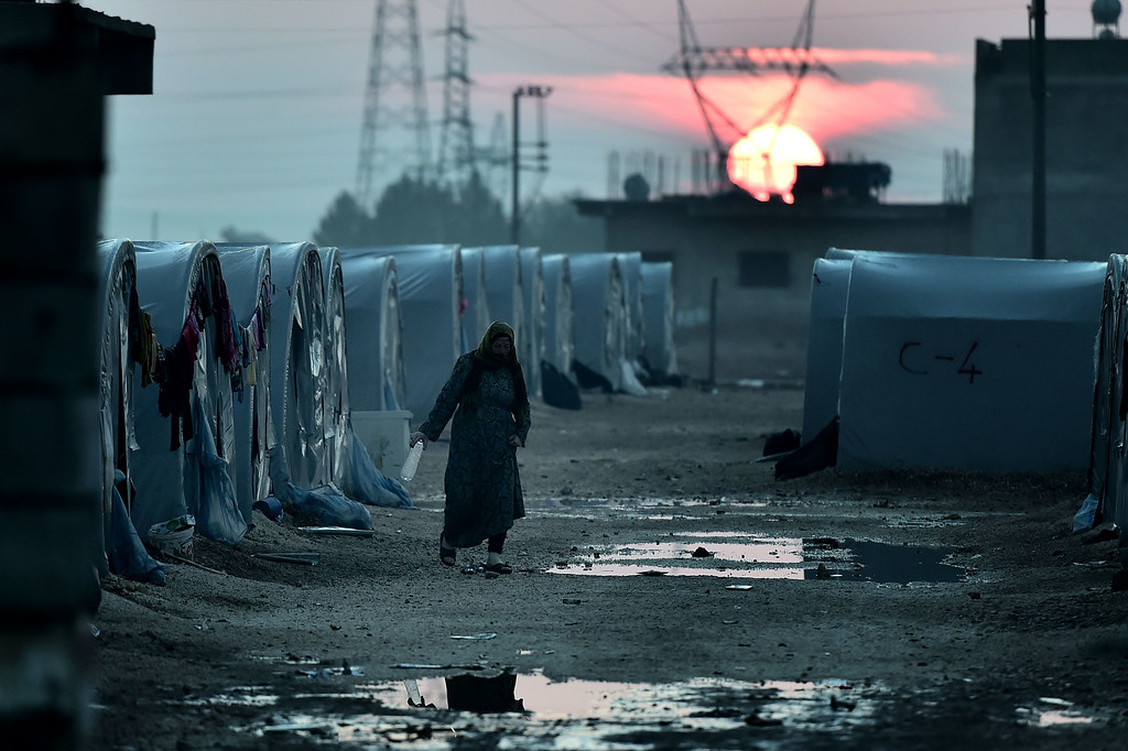 . A Syrian Kurdish woman walks in a refugee camp in the town of Suruc, Sanliurfa province, on October 17, 2014.   AFP PHOTO / ARIS  MESSINIS/AFP/Getty Images
