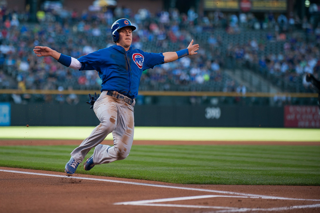 . DENVER, CO - AUGUST 06:  Chris Coghlan #8 of the Chicago Cubs begins a slide to score a run on a sacrifice fly in the first inning of a game against the Colorado Rockies at Coors Field on August 6, 2014 in Denver, Colorado.  (Photo by Dustin Bradford/Getty Images)