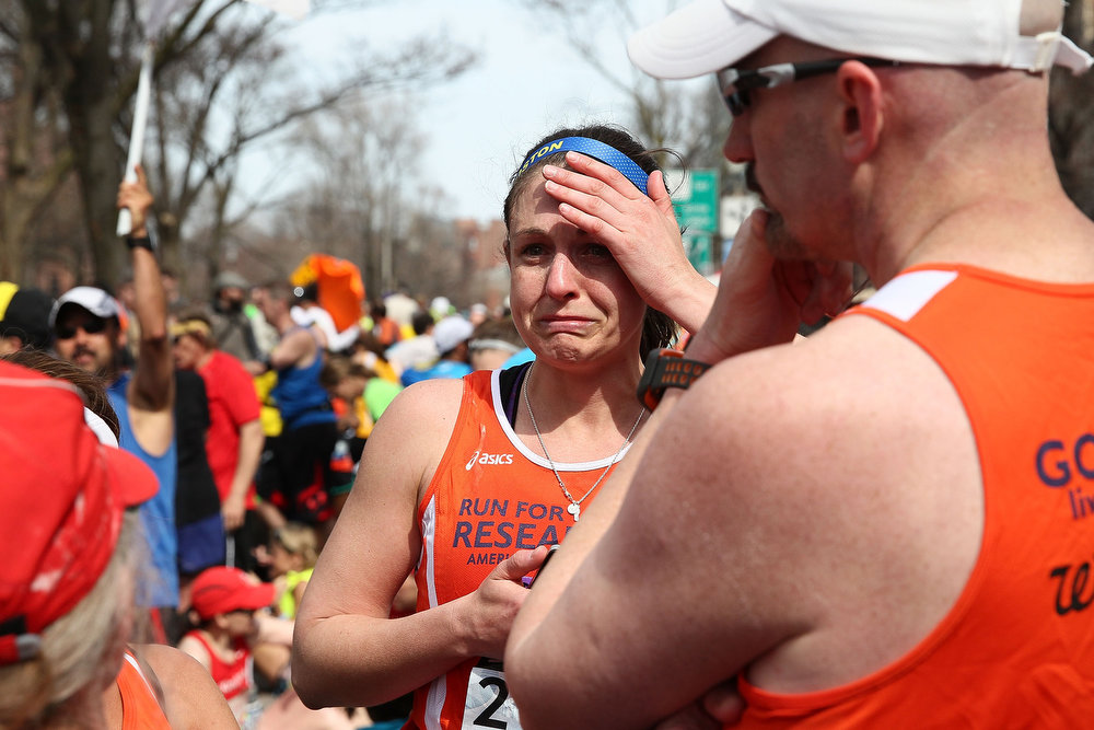 . A runner reacts near Kenmore Square after two bombs exploded during the 117th Boston Marathon on April 15, 2013 in Boston, Massachusetts. Two people are confirmed dead and at least 23 injured after two explosions went off near the finish line to the marathon.  (Photo by Alex Trautwig/Getty Images)