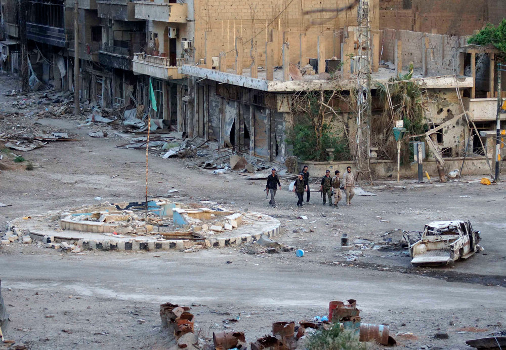 . Members of the Free Syrian army walk with their weapons along a street filled with debris in Deir al-Zor on April 15, 2013. Picture taken April 15, 2013. REUTERS/ Khalil Ashawi