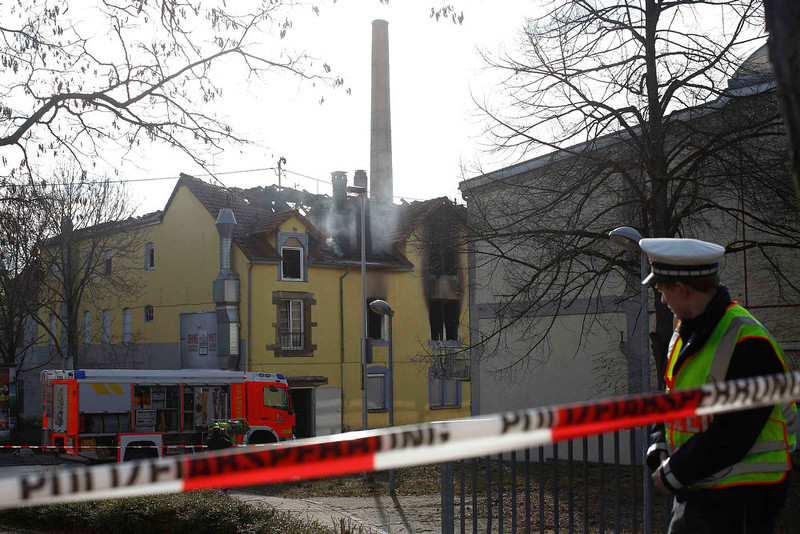 . A police man looks at a smoldering building following a fire in Backnang, Germany on March 10, 2013. At least eight people, including seven children, died after a fire broke out in a building in the southern German province of Baden-Wuerttemberg on Sunday. The cause of the fire is not yet known. REUTERS/Lisi Niesner