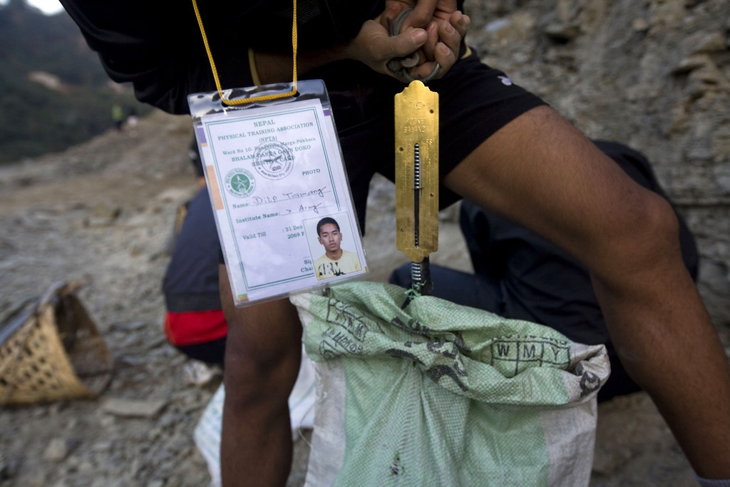 . A Nepalese youth measures the weight of a stone bag that will be carried during a physical training session organized by a private institute in Phokhara, who prepares youth men for the British Gurkha soldier recruitment selection, at Malam Mountain in Kaski district, Nepal, 18 November 2012. The British Gurkha soldier recruitment selection process started on 23 November and runs untill the end of December 2012 at British Gurkha camp situated in Pokhara City, Nepal. Around 125 youths will be selected from more than three thousands participants. Those selected will join the British Army, a selection which carries much prestige and admiration throughout Nepalese society.  EPA/NARENDRA SHRESTHA