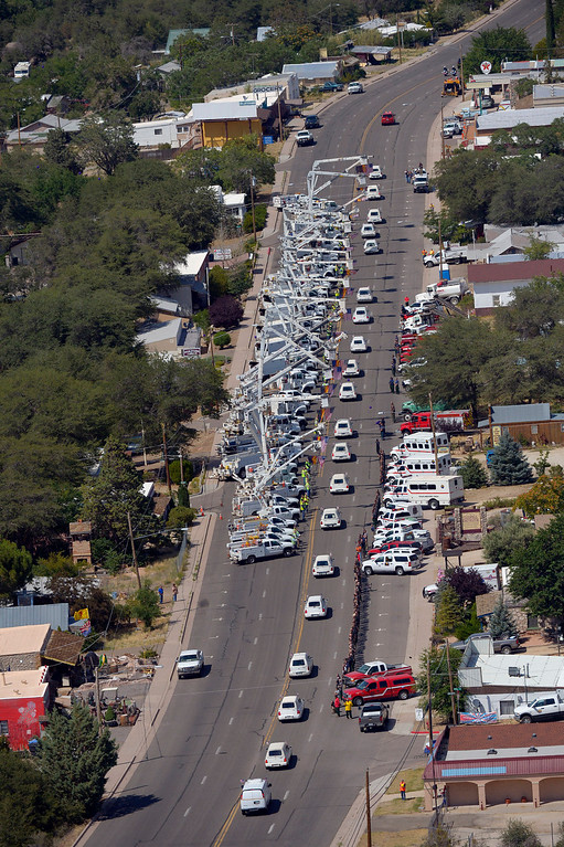 . A procession of 19 hearses drives by, Sunday, July 7, 2013, in Yarnell, Ariz, The elite crew of firefighters were overtaken by the out-of-control blaze as they tried to protect themselves from the flames under fire-resistant shields last Sunday. (AP Photo/Mark J. Terrill)