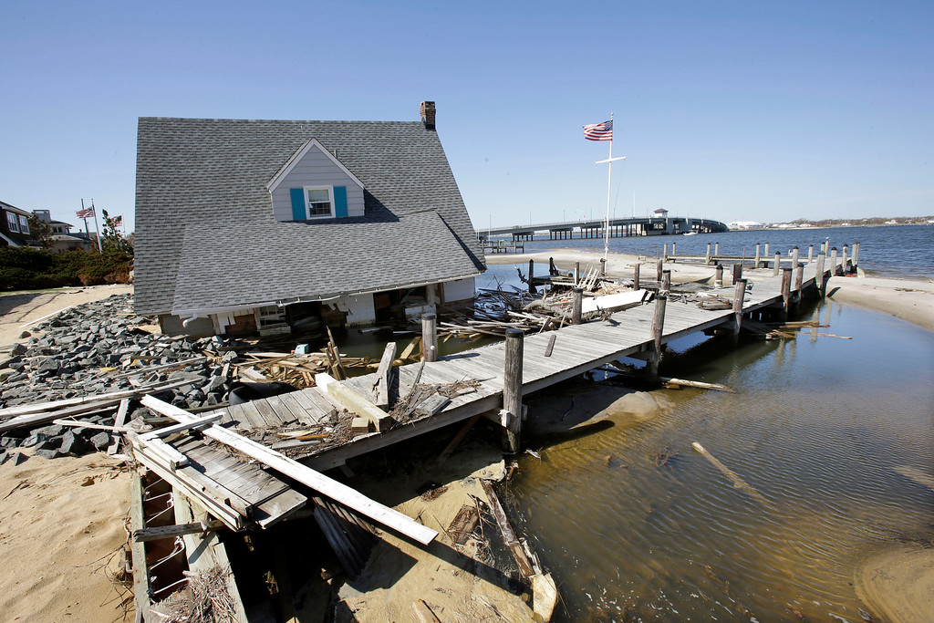 . A home rests next to a pier in Barnegat Bay, Thursday, April 25, 2013, near the Mantoloking Bridge in Mantoloking, N.J., after it was swept away last October by Superstorm Sandy. Six months after Sandy devastated the Jersey shore and New York City and pounded coastal areas of New England, the region is dealing with a slow and frustrating, yet often hopeful, recovery. (AP Photo/Mel Evans)