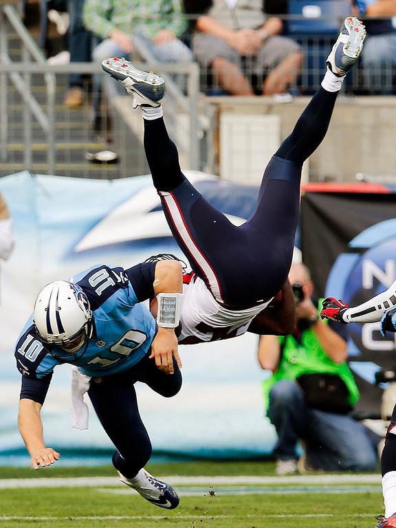 . Tennessee Titans quarterback Jake Locker (10) tackles Houston Texans inside linebacker Tim Dobbins (52) after Dobbins intercepted a pass by Locker in the second quarter of an NFL football game on Sunday, Dec. 2, 2012, in Nashville, Tenn. (AP Photo/Joe Howell)
