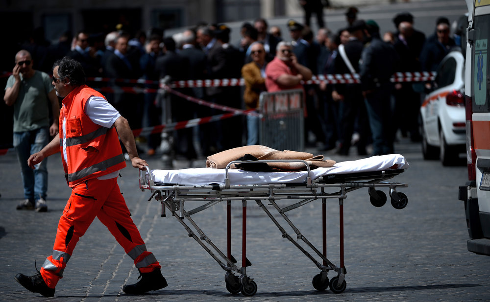. A doctor carriers a stretcher after a Carabiniere police officer was shot by a man in front of Chigi Palace in Rome on April 28, 2013. Gunshots were fired in front of the Italian prime minister\'s office in Rome on Sunday as the new government of Enrico Letta was being sworn in at the president\'s palace, Quirinale, around a kilometer away.   FILIPPO MONTEFORTE/AFP/Getty Images