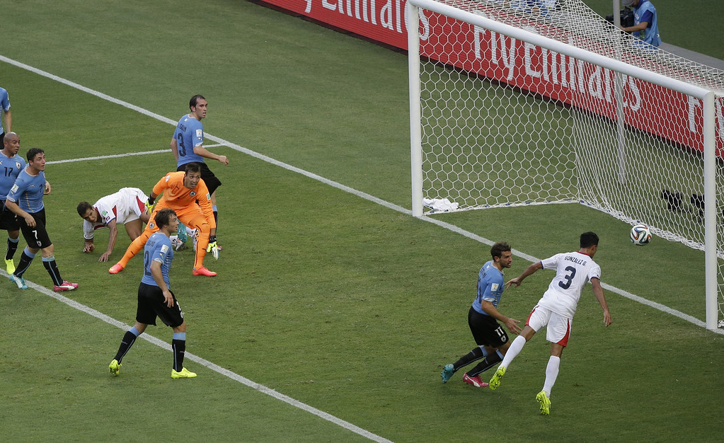 . Costa Rica\'s Giancarlo Gonzalez, right, heads the ball past the goal during the group D World Cup soccer match between Uruguay and Costa Rica at the Arena Castelao in Fortaleza, Brazil, Saturday, June 14, 2014.  (AP Photo/Sergei Grits)