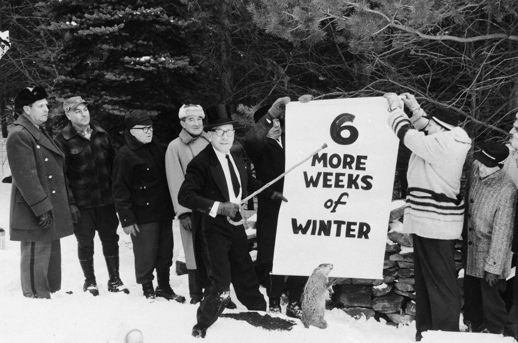 . Sam Light, center, president of the Punxsutawney Groundhog Club, points to a sign held by members of the club in Gobbler\'s Knob, Punxsutawney, Pennsylvania, Jan. 1961.  They posed for the picture a few days before Groundhog Day, Feb. 2, with a stuffed stand-in for Punxsutawney Phil.  (AP Photo)