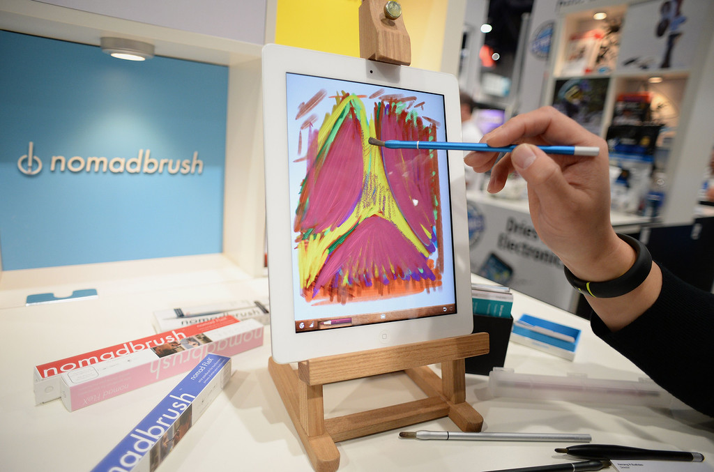 . NomadBrush founder and CEO Don Lee uses a NomadBrush Flex paintbrush stylus and an oil painting app to paint on an iPad at the 2014 International CES in Las Vegas, Nevada, January 8, 2014.  Each bristle of the paintbrush stylus, which was recently released and is priced at USD $29, is conductive. AFP PHOTO / Robyn Beck/AFP/Getty Images